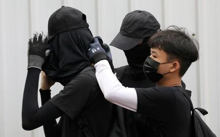 FILE PHOTO: Anti-government protesters adjust their masks during a protest at Wong Tai Sin district, in Hong Kong