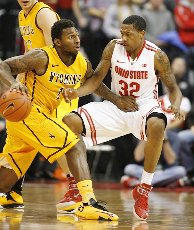 Ohio State's Lenzelle Smith, Jr. (32) tries to slow down Wyoming's Charles Hankerson (1) during the second half of an NCAA college basketball game, Monday, Nov. 25, 2013, in Columbus, Ohio. (AP Photo/Mike Munden)