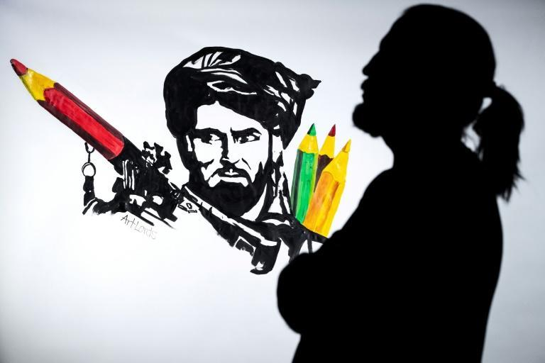 Afghan artist and co-founder of the ArtLords collective, Farshad, poses next to a piece of work by the group (AFP/JOEL SAGET)