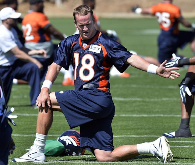 Denver Broncos quarterback Peyton Manning stretches during an NFL football organized team activity, Wednesday, May 28, 2014, in Englewood, Colo., (AP Photo/Jack Dempsey)