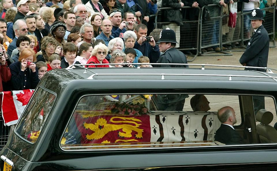 LONDON, UNITED KINGDOM:  The Queen Mother's coffin passes mourners and police before being carried to The Queens Chapel in St. James Palace in London, Tuesday 02 April 2002, where it will lay until Friday 05 April before moved to Westminister Hall. The funeral will be held in Westminister Abbey on Tuesday 09 April.   AFP PHOTO   GERRY PENNY (Photo credit should read GERRY PENNY/AFP via Getty Images)
