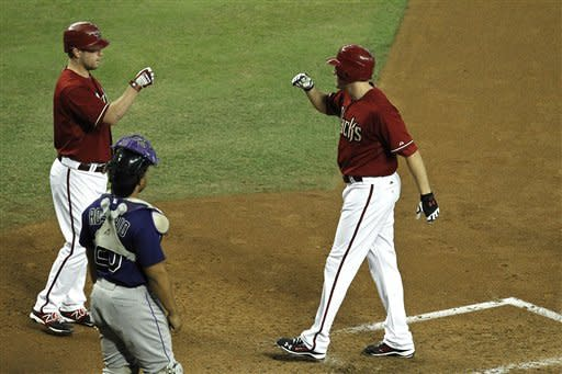 Arizona Diamondbacks' A.J. Pollock, right, celebrates his home run with teammate Aaron Hill, left, as Colorado Rockies' Wilin Rosario looks on during the third inning of a baseball game on Wednesday, Oct. 3, 2012, in Phoenix.( AP Photo/Ross D. Franklin)