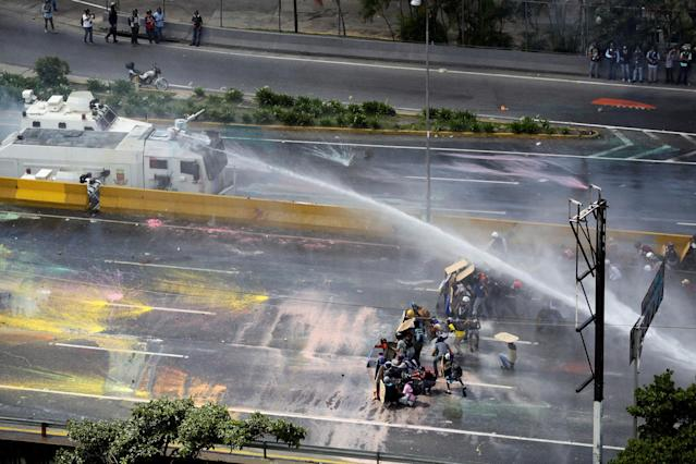 <p>Opposition supporters clash with riot security forces while rallying against President Nicolas Maduro in Caracas, Venezuela, May 18, 2017. (Christian Veron/Reuters) </p>