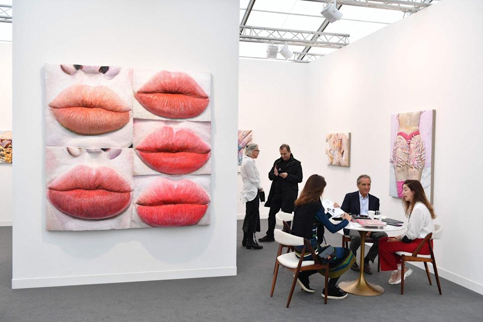 Exhibitors work at a stall of artworks by US artist Gina Beavers during the Frieze Art Fair - AFP