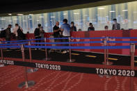 People arriving for the 2020 Summer Olympics wait for their credentials to be validated before they can leave Haneda Airport in Tokyo, Monday, July 19, 2021. (AP Photo/Natacha Pisarenko)