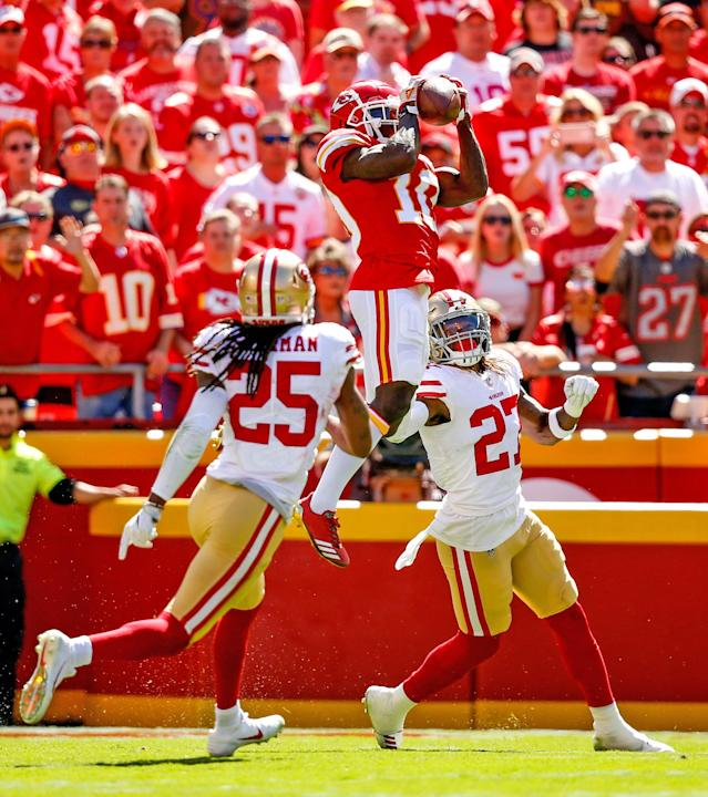 <p>Tyreek Hill #10 of the Kansas City Chiefs leaps in the air to make a catch against Adrian Colbert #27 and Richard Sherman #25 of the San Francisco 49ers during the second quarter fo the game at Arrowhead Stadium on September 23rd, 2018 in Kansas City, Missouri. (Photo by David Eulitt/Getty Images) </p>
