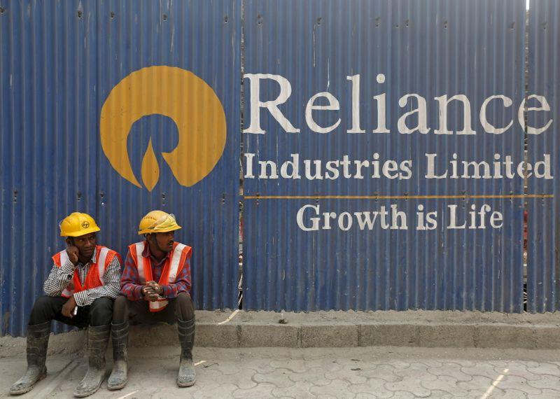 FILE PHOTO: Labourers rest in front of an advertisement of Reliance Industries Limited at a construction site in Mumbai