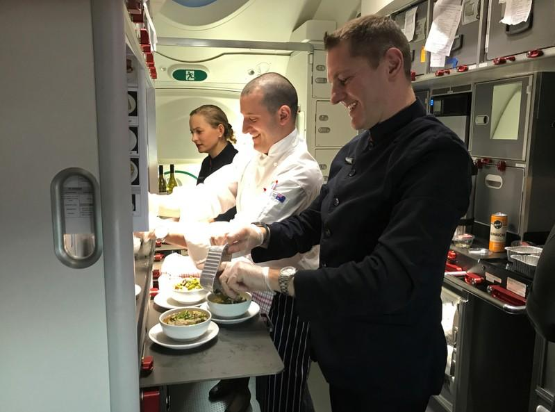 Crew members prepare food on board Qantas flight QF7879, flying direct from London to Sydney
