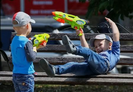 Children play with water guns in a park, central Bakhmut