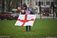 A man holds an English flag in Parliament Square, in London, Thursday, Dec. 31, 2020. Eleven months after Britain's formal departure from the EU, Brexit becomes a fact of daily life on Friday, once a transition period ends and the U.K. fully leaves the world's most powerful trading bloc. (AP Photo/Alberto Pezzali)