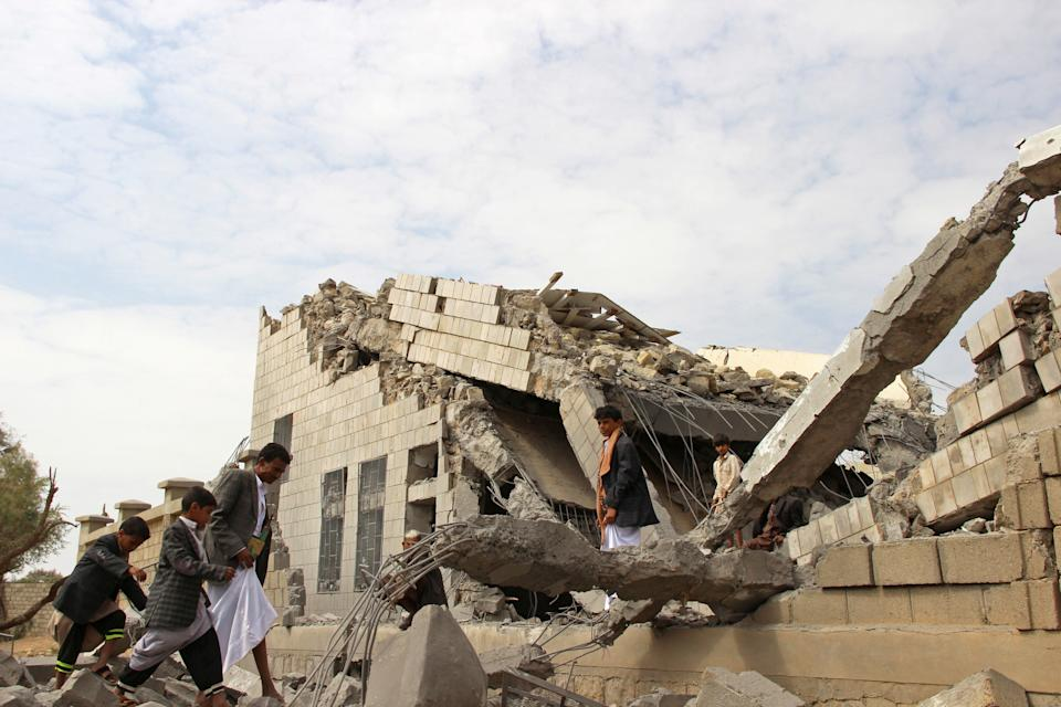 People walk on the rubble of a school destroyed by a Saudi-led air strike in an outskirt of the northwestern city of Saada, Yemen September 14, 2016. REUTERS/Naif Rahma