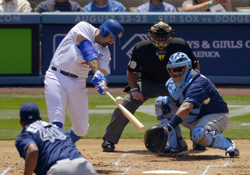 Los Angeles Dodgers' Adrian Gonzalez hits a two-run home run as Tampa Bay Rays starting pitcher Roberto Hernandez, front, and catcher Jose Molina and home plate umpire Paul Nauert watch during the first inning of a baseball game Saturday, Aug. 10, 2013, in Los Angeles. (AP Photo/Mark J. Terrill)