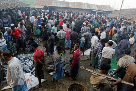 Rohingya men are pictured at a fish market in Sittwe in the state of Rakhine