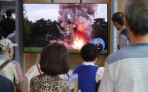 People watch a TV showing a file image of a North Korea's missile launch during a news program at the Seoul Railway Station in Seoul, South Korea, Tuesday, Sept. 10, 2019. North Korea launched at least two unidentified projectiles toward the sea on Tuesday, South Korea's military said, hours after the North offered to resume nuclear diplomacy with the United States but warned its dealings with Washington may end without new U.S. proposals.(AP Photo/Ahn Young-joon)