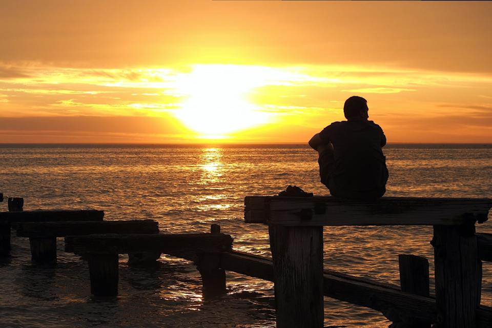 Man sitting on dock at sunset looking at water