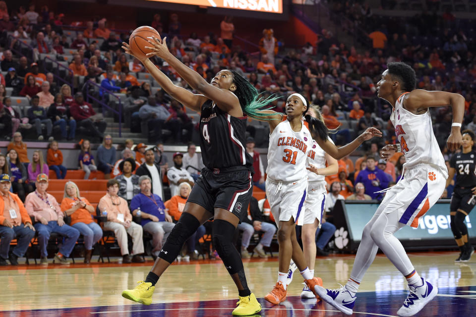 South Carolina's Aliyah Boston (4) grabs the ball while defended by Clemson's Shania Meertens (31) and Kobi Thorton during the first half of an NCAA college basketball game Sunday, Nov. 24, 2019, in Clemson, S.C. (AP Photo/Richard Shiro)