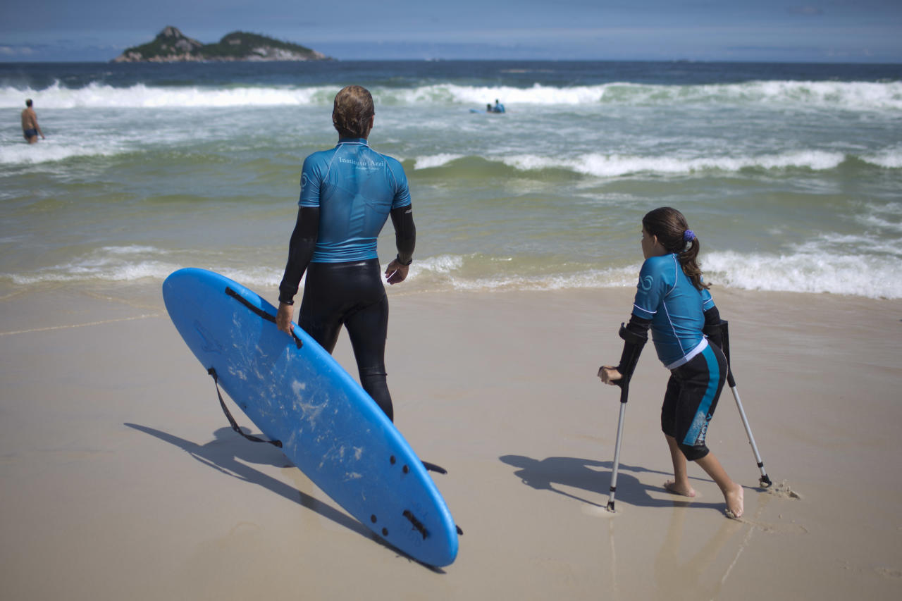 In this March 16, 2013 photo, Camila Fuchs, right, is accompanied by an AdaptSurf volunteer as they head out to sea to catch some waves, at Barra da Tijuca beach in Rio de Janeiro, Brazil. AdaptSurf is a Rio-based non-governmental organization that aims to make beaches accessible to the disabled and encourage them to practice water sports. The organization is the first of its kind in Brazil. (AP Photo/Felipe Dana)