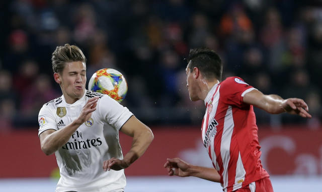 Real Madrid's Marcos Llorente, left, duels for the ball with Girona's Bernardo Espinosa during a Spanish Copa del Rey soccer match between Girona and Real Madrid at the Montilivi stadium in Girona, Spain, Thursday, Jan. 31, 2019. (AP Photo/Manu Fernandez)