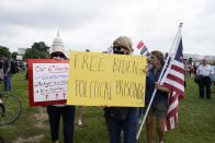 """People hold signs as others leave a rally near the U.S. Capitol in Washington, Saturday, Sept. 18, 2021. The rally was planned by allies of former President Donald Trump and aimed at supporting the so-called """"political prisoners"""" of the Jan. 6 insurrection at the U.S. Capitol. (AP Photo/Jose Luis Magana)"""