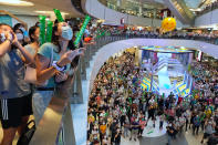 People react as they watch Siobhan Bernadette Haughey of Hong Kong swim in the women's 100-meter freestyle final at the 2020 Summer Olympics, at a shopping mall in Hong Kong, Friday, July 30, 2021. Haughey, born in Hong Kong four months after the 1997 handover, now has two silver medals from Tokyo, becoming the city's first-ever multiple medalist. Hong Kong's haul of treasure from Tokyo, with a gold also won in men's fencing, outshines the one gold, one silver and one bronze that Hong Kong accumulated through all of its previous Olympic appearances since its 1952 debut at the Helsinki Games. (AP Photo/Vincent Yu)