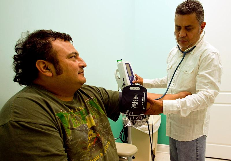 Rafael Carcache checks the blood pressure of a Hispanic man at the Slocomb Health Clinic.