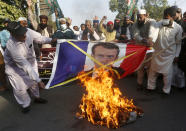 Supporters of Sunni Tehreek, a religious group, burn a representation of a French flag with a defaced image of French President Emmanuel Macron during a protest against the French president and republishing of caricatures of the Prophet Muhammad they deem blasphemous, in Lahore, Pakistan, Sunday, Nov. 1, 2020. (AP Photo/K.M. Chaudary)