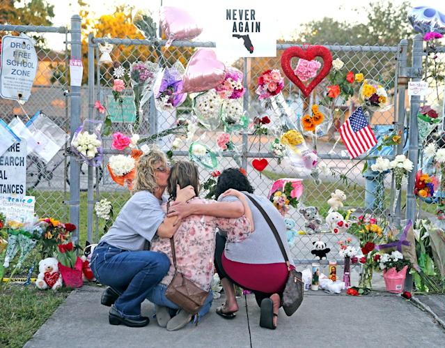 <p>Shari Unger kisses Melissa Goldsmith as Giulianna Cerbono lights candles at a memorial at Marjory Stoneman Douglas High School on Sunday, February 18, 2018. (Photo: Charles Trainor Jr./Miami Herald/TNS via Getty Images) </p>