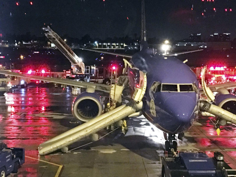 This Monday, Feb. 12, 2018 photo by JC Arkham shows a Southwest Airlines jet with emergency slides deployed following Arkham's and his wife's evacuation from the plane at John Wayne Airport in Santa Ana, Calif. An airport official says one of four emergency slides failed to deploy during a fire in the plane's auxiliary power unit just after pushback, and the malfunction did not hinder the evacuation. The fire was extinguished by the plane's fire suppression system. (JC Arkham via AP)