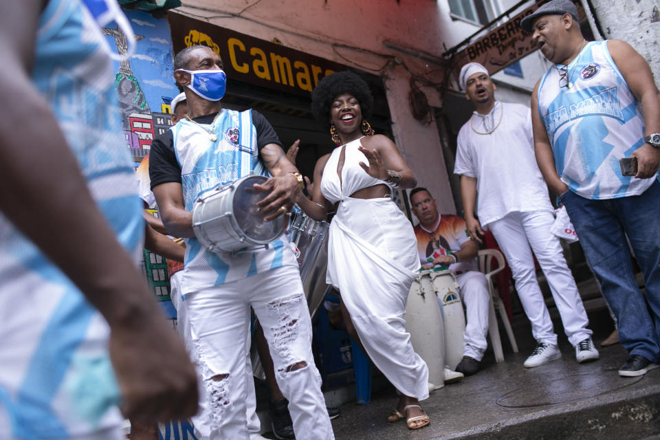 Members of the Mocidade Unida do Santa Marta samba school dance for a ceremony marking Black Consciousness Day in the Santa Marta favela of Rio de Janeiro, Brazil, Friday, Nov. 20, 2020. Brazilians celebrate the holiday with Afro-Brazilian dance, music and religious ceremonies, reflecting the deep cultural and social ties of the Black community to the country's history and honor legendary anti-slave leader Zumbi dos Palmares on the day of his death. (AP Photo/Bruna Prado)