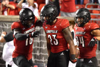 Louisville running back Trevion Cooley (23) celebrates with wide receiver Justin Marshall (18) and tight end Dez Melton (84) following his touchdown during the second half of an NCAA college football game against Central Florida in Louisville, Ky., Friday, Sept. 17, 2021. (AP Photo/Timothy D. Easley)
