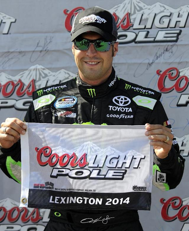 Sam Hornish Jr. holds the pole position flag after qualifying for the NASCAR Nationwide Series Nationwide Children's Hospital 200 auto race at Mid-Ohio Sports Car Course on Saturday, Aug. 16, 2014 in Lexington, Ohio. (AP Photo/Tom E. Puskar)