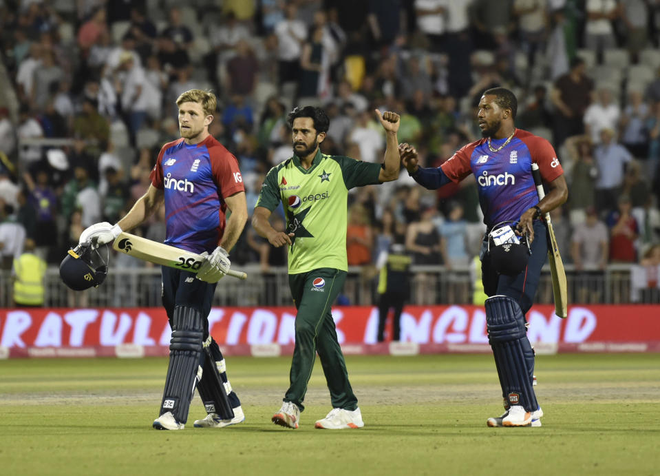 England's David Willey, left, Chris Jordan, right, and Pakistan's Hasan Ali, center, leave the field at the end of the third Twenty20 international cricket match against Pakistan at Old Trafford in Manchester, Tuesday, July 20, 2021. (AP Photo/Rui Vieira)
