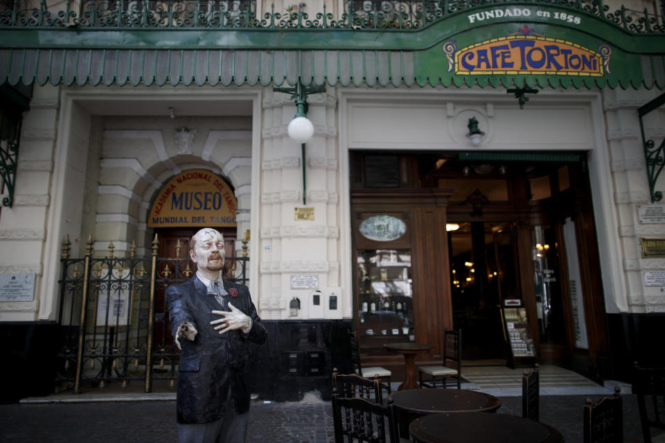 "A statue with a broken arm, of Horacio Ferrer, an Uruguayan-Argentine poet stands outside Cafe Tortoni amid the new coronavirus pandemic in Buenos Aires, Argentina, Tuesday, Nov. 10, 2020. ""This year has been very hard ... Before the cafe was always full, you had to wait to get in,"" said Nicolas Prado, one of the managers of Cafe Tortoni, located in the center the Argentine capital, which is known for its European flair. (AP Photo/Natacha Pisarenko)"