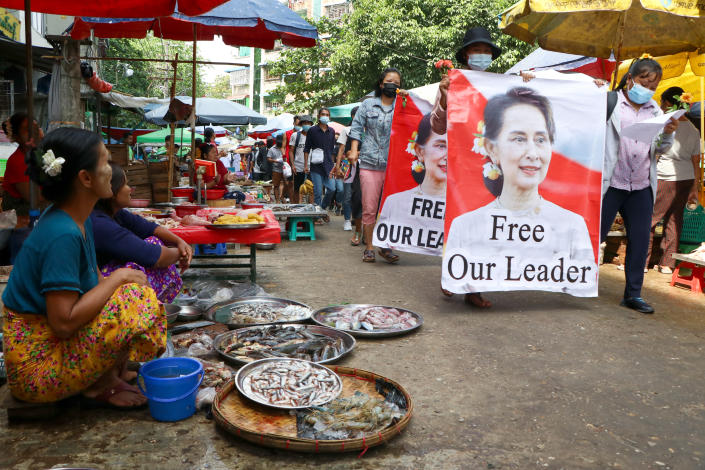 FILE - In this April 8, 2021, file photo, anti-coup protesters walk through a market with images of ousted Myanmar leader Aung San Suu Kyi in Yangon, Myanmar. Aid workers and activists are warning Myanmar's political upheavals could cause a regional refugee crisis as political strife following a Feb. 1 coup displace growing numbers of people who have lost their livelihoods. coming in a couple hours. (AP Photo, File)