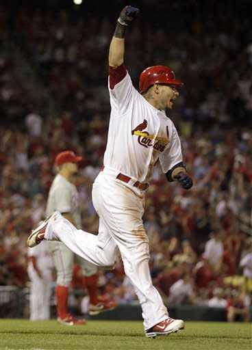 St. Louis Cardinals' Yadier Molina, front, celebrates as he rounds the bases after hitting a two-run home run off Philadelphia Phillies starting pitcher Joe Blanton, rear, during the fifth inning of a baseball game Thursday, May 24, 2012, in St. Louis. (AP Photo/Jeff Roberson)