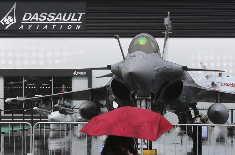 A visitor walks in front of a Dassault Rafale fighter on the first day of the rain-soaked 50th Paris Air Show, at Le Bourget airport near Paris