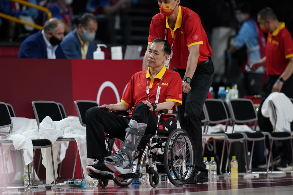 China head coach Limin Xu is brought to the court in a wheelchair during a women's basketball preliminary round game against Australia at the 2020 Summer Olympics in Saitama, Japan, Friday, July 30, 2021. (AP Photo/Eric Gay)