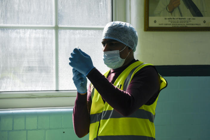 Dr Talib Abubacker prepares a dose of the AstraZeneca COVID-19 vaccine, at the Guru Nanak Gurdwara Sikh temple, on the day the first Vaisakhi Vaccine Clinic is launched, in Luton, England, Sunday, March 21, 2021. (AP Photo/Alberto Pezzali)