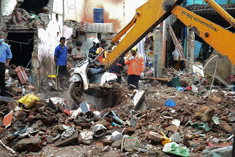 Civil authority and rescue personnel search for survivors in the debris of a building that collapsed following heavy monsoon rains, in Mumbai on 10 June 2021 (AFP via Getty Images)