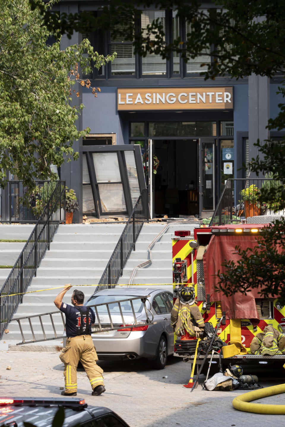 A firefighter carries a ladder past the damaged leasing center following an apartment building explosion, Sunday, Sept. 12, 2021, in Dunwoody, Ga., just outside of Atlanta. (AP Photo/Ben Gray)