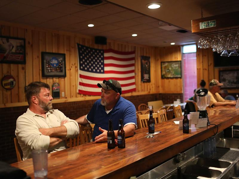 Unemployed coal miners Todd Hatfield (L) and Dave Houck talk at Hatfield's bar and restaurant in Gilbert, West Virginia May 22, 2014.
