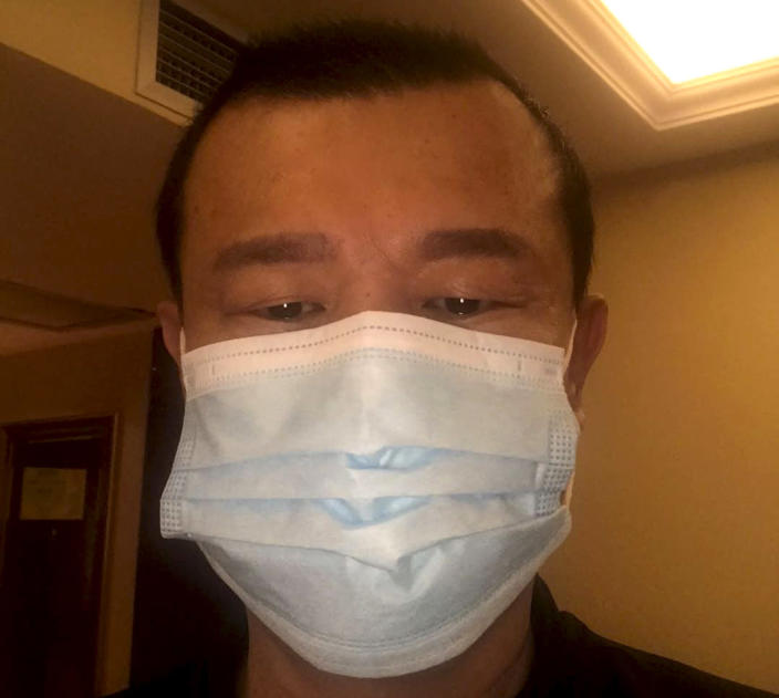 In this photo taken on Feb 24, 2020, and released by Chen Chi-chuan, Chen Chi-chuan, 51, a Taiwanese electrical and plumbing contractor poses for a photo in his room at the Vienna International Hotel where he's lived in since Jan. 28 in Shiyan city in central China's Hubei province. Chen and about 1,000 other Taiwanese citizens are stuck behind doors in locked-down Chinese cities because their government cannot agree with China on how to arrange charter flights. Some are losing business income, risking too many absences from work and wondering how their children, if also stranded, will make up lost school days. (Chen Chi-chuan via AP)