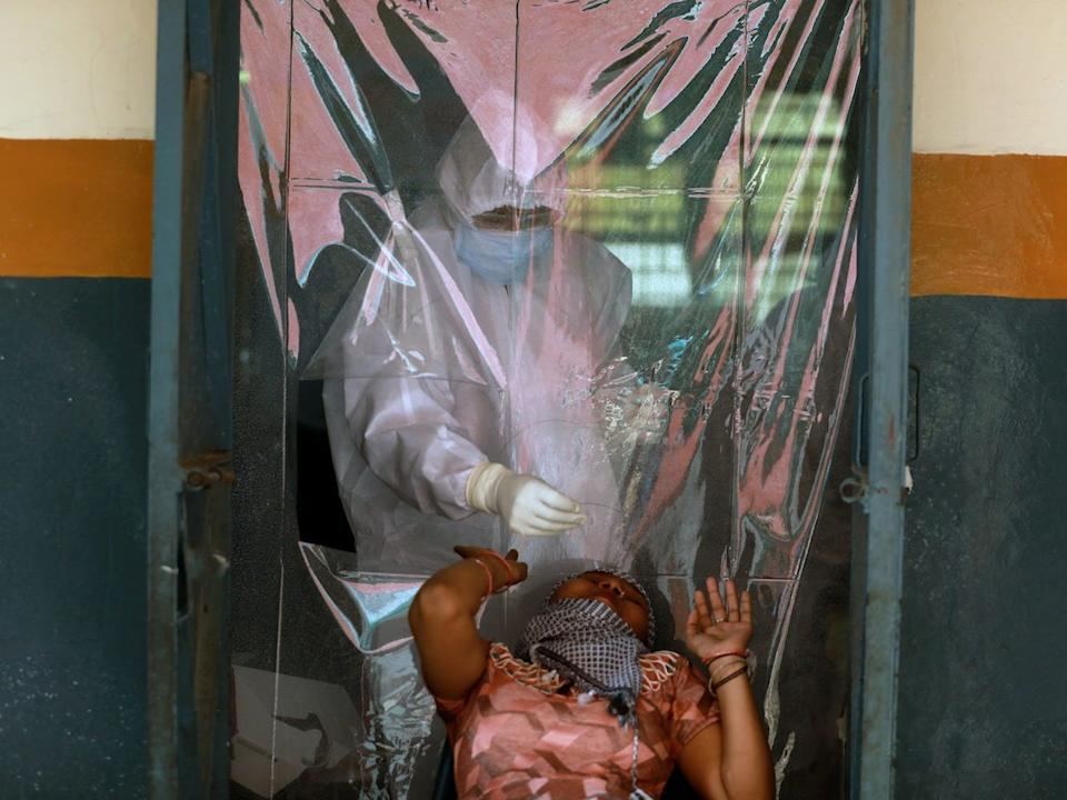 A medical worker collects a sample from a woman using a swab in New Delhi, India, on June 30, 2020.