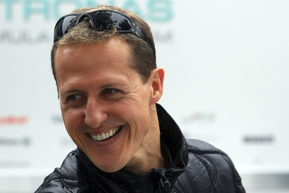 Mercedes Formula One driver Michael Schumacher of Germany smiles at the back of the pits ahead of this weekend's Australian Grand Prix in Melbourne March 24, 2011. The Australian F1 race, to be held on March 27, is the first race of the season after the event was cancelled in Bahrain due to political unrest.  REUTERS/Scott Wensley (AUSTRALIA - Tags: SPORT MOTOR RACING)