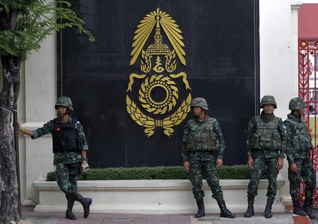 Thai soldiers stand guard outside the Royal Thai Army Headquarters as members of the Radio and Satellite Broadcasters gather in Bangkok