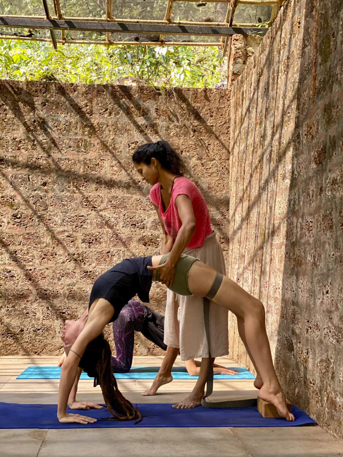 """Yoga teacher Sharanya Narayanan guides a student at Mojigao in Goa, India, Dec.24, 2020. Narayanan was teaching in multiple locations but had to switch to virtual lessons during the lockdown. When wellness centers were allowed to reopen in August, only one of her jobs came back — her own private class.""""The pandemic has changed everybody's life – including mine,"""" she said. Goans are mourning the loss of their livelihoods and possibly their way of life to the pandemic and travel restrictions. (Sheetal Mallar/Sharanya Narayanan via AP)"""