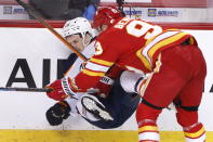 Edmonton Oilers' Josh Archibald, left, takes a hit from Calgary Flames' Sam Bennett during the first period of an NHL hockey game Saturday, April 10, 2021, in Calgary, Alberta. (Larry MacDougal/The Canadian Press via AP)
