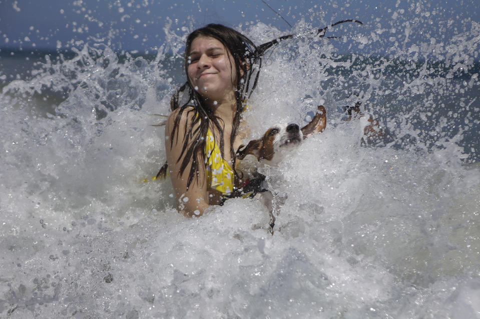 Mariana Rojas plays with her dog Sussy in the waves off Los Angeles beach after it recently reopened following a lockdown to contain the spread of COVID-19 in La Guaira, Venezuela, Friday, Oct. 23, 2020. Strict quarantine restrictions forced the closure of beaches across the country in March and reopened this week. (AP Photo/Matias Delacroix)