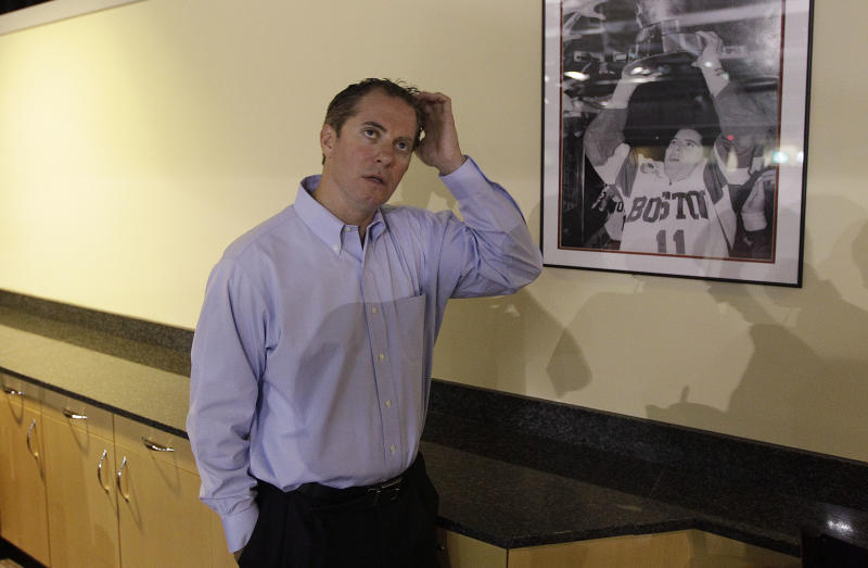 This photo made Aug. 18, 2011 shows Boston University assistant men's hockey coach Mike Bavis remembering his twin brother , Mark, who was killed on United flight 175 when it crashed into the World Trade Center on Sept. 11, 2001, while standing near a photograph of his brother in a players suite dedicated to him in the Agganis Arena on the schools campus in Boston. Mary Bavis believes there are still more to blame for the death of her son Mark _ more who have not been punished, or held accountable, or even publicly identified.   (AP Photo/Stephan Savoia)