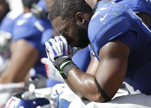 FILE - In this Sunday, Sept. 22, 2013, file photo, New York Giants' Justin Tuck sits on the bench during the second half of an NFL football game against the Carolina Panthers in Charlotte, N.C. Their 0-3 start is their worst since 1996 and the worst of the Tom Coughlin era. Their performance in a 38-0 loss to the Carolina Panthers on Sunday was abysmal. (AP Photo/Bob Leverone, File)